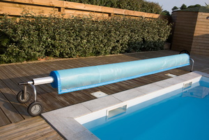 Rolled pool cover at the end of an inground pool