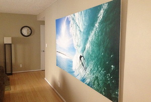 A mural of a surfer hanging on an apartment wall.
