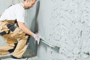 man smoothing plaster wall