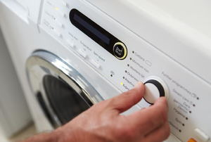 a hand turning a switch on a Washing Machine