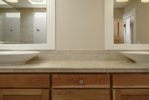 A bathroom vanity with cabinets, mirrors, and double sinks.