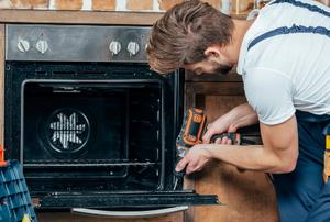 man fixing oven door with screw gun