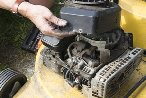 hands repairing lawn mower engine