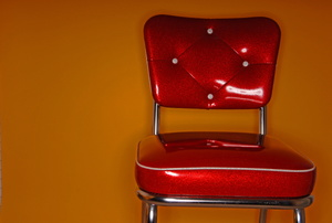 A red vinyl chair against an orange wall.