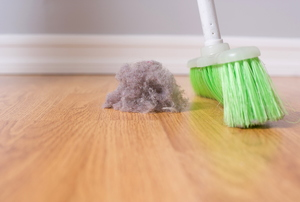 A broom sweeping up a dust bunny that's an indoor air pollutant.