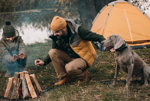 man, child, and dog camping