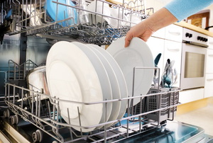 A homeowner unloading clean dishes from their dishwasher.