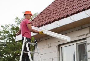 A man hanging a gutter on the roofline of a house.