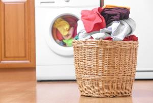 A hamper next to a washing machine.