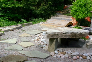 A rock-garden with flag stones and a stone table.