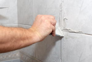 A man works on grout lines.