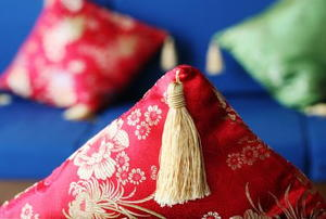 tassel hanging down from a red and gold throw pillow