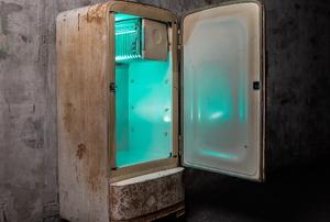 broken old refrigerator with light inside