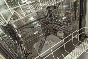 With the dishwasher open and the bottom rack pulled out, the lower dishwater spray arm can be seen.