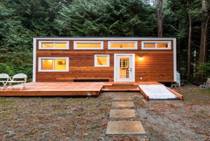 A wood paneled tiny home in the forest