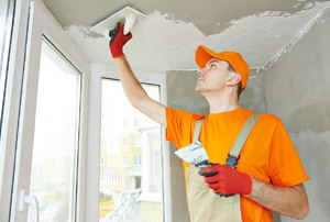 A man applying texture to a ceiling.