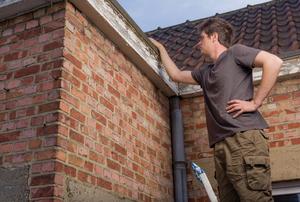 A man inspecting a gutter