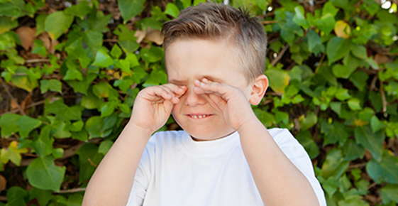 Image of a boy rubbing his eyes.