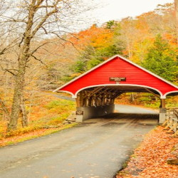 Red, covered bridge with fall foliage
