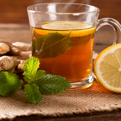 Hot cup of tea next to lemon slice, mint leaf, and ginger root