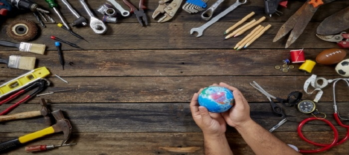 hands holding a globe surrounded by tools