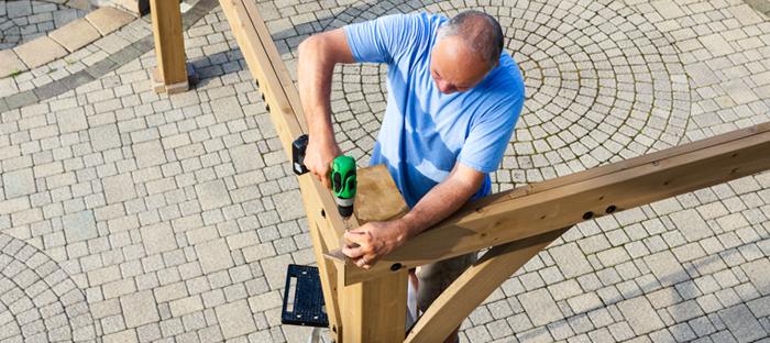 Man Using Drill on Wooden Pergola Frame