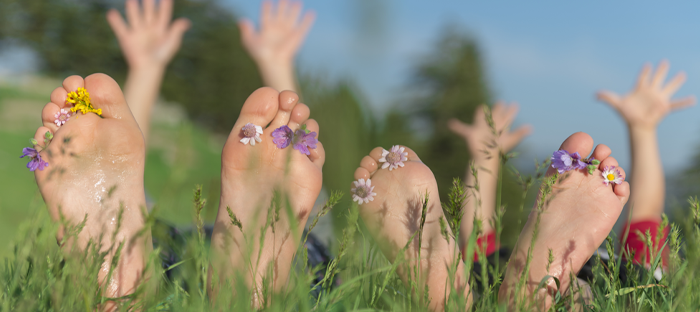 Two people laying on the grass with flowers in their toes