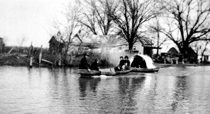 people in boat on flooded streets