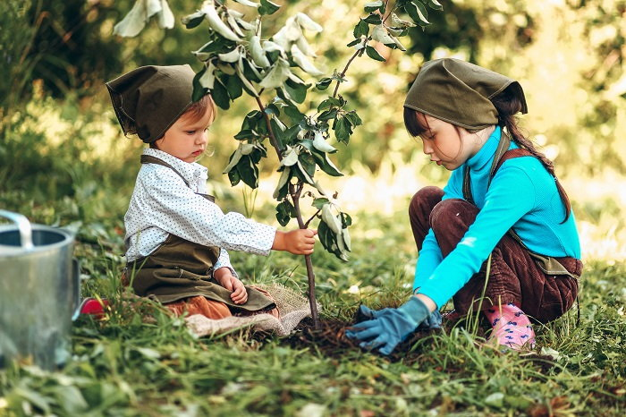 two little girls planting a tree
