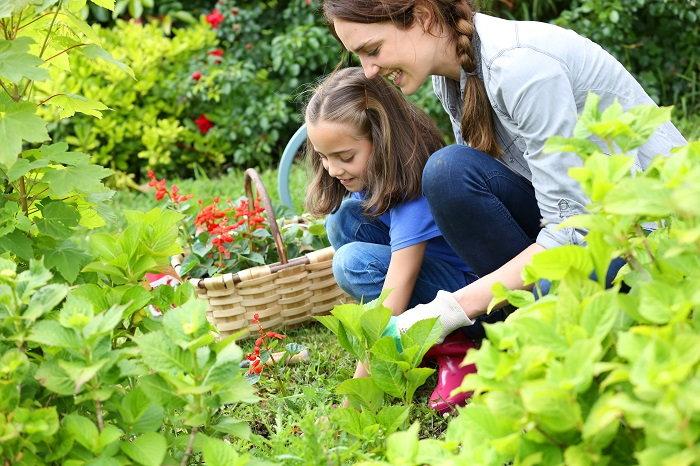 mother teaching her daughter how to garden