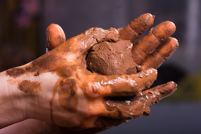 Pair of hands holding wet clay