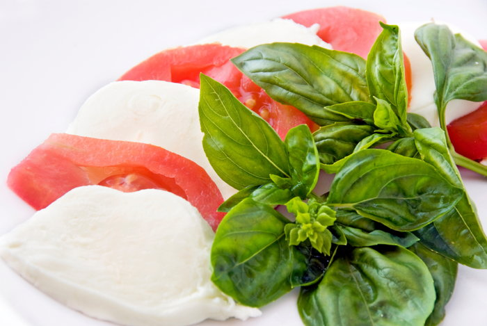 Basil leaves with cheese and tomato slices