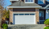 Front of a house with white garage door and brick façade.