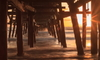 sun setting on an ocean under a wooden pier