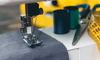 sewing machine stitching grey fabric