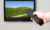 person pushing button on remote aimed at TV on the wall