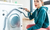 woman next to the back of a washing machine