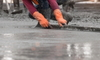 gloved hands using a long board to smooth concrete