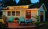 A shed in a backyard with patio furniture and lights.