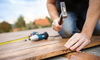 A DIYer hammering a nail into a piece of wood with a drill beside him.