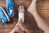 pair of feet and pair of shoes with gauze around one foot.