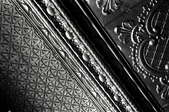A close-up of stamped ceiling tiles in black and white.