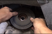a man's hands pulling the crankshaft pulley out of an engine