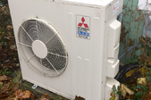 A ductless heating unit on the outside of a home.