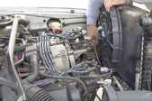man checking engine components