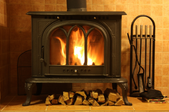 a wood stove with wood beneath it