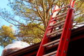 A red ladder propped up against a brown gutter with a bag of leaves on top of the roof.