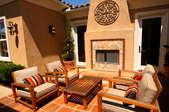 An earth-tone patio with a stucco fireplace.