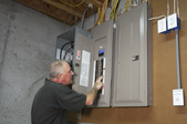 man checking fuses on a circuit box