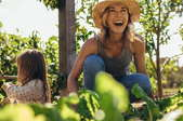 laughing woman with girl in vegetable patch